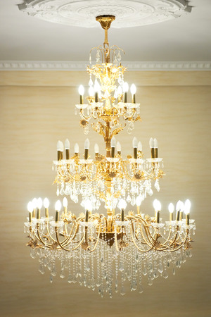 chandelier: Beautiful crystal ancient chandelier in a hall. Lamp with soft yellow light