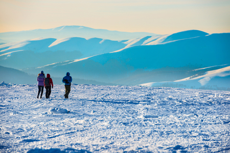 sunrise mountain: People walking at sunset in winter mountains covered with snow