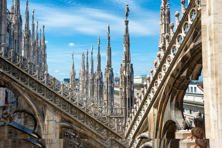 roof: White marble statues on the roof of famous Cathedral Duomo di Milano on piazza in Milan, Italy