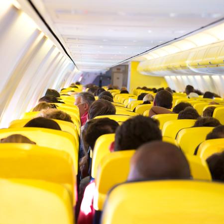 asiento: Aisle inside a plane. Interior with passengers on the seats Foto de archivo