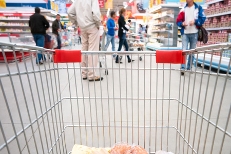 shopping trolleys: Shopping cart, trolley in a big supermarket with blurred people