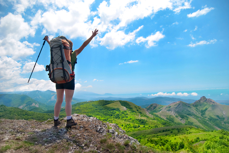 hiking stick: Young happy woman with hiking stick, backpack standing on the rock with raised hands and looking to green landscape
