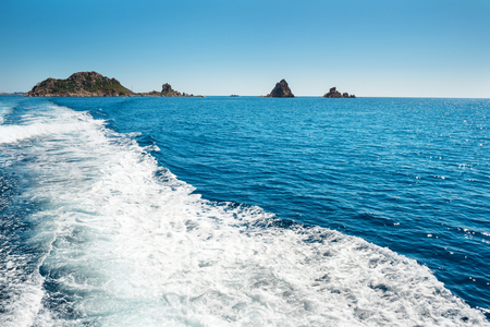 wake: Waves on blue sea behind the speed boat water in sunny day Stock Photo