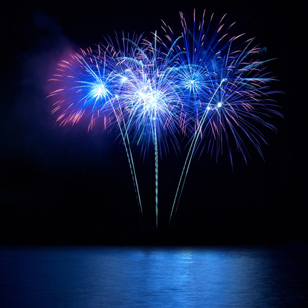 검은 하늘 배경에 반사와 물 위에 푸른 불꽃 놀이