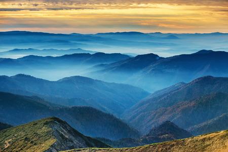Blaue Berge und Hügel über schönen Sonnenuntergang Standard-Bild