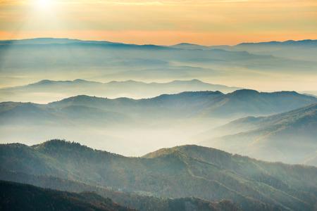 ブルー マウンテンズとオレンジ色の夕日の下の丘
