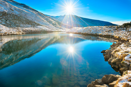 sunrays: Beautiful blue lake in the mountains, morning sunrise time. Landscape with snow shining sun