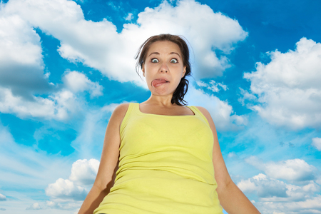 Pretty young girl with funny face expression over blue sky with clouds photo
