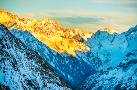 snowy mountain: Sunset in winter mountains covered by snow. Orange peaks of the ridge