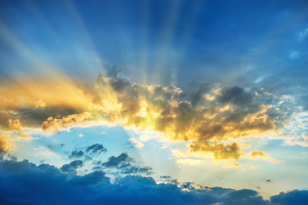 Sunset over beautiful blue sky with sun shining through clouds 写真素材