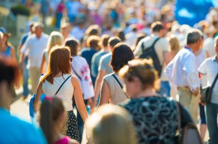 Menge von Menschen auf der sonnigen und belebten Straße zu Fuß. Weicher Fokus