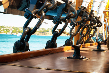old ship: Black metal rigging and ropes on a deck of sail ship