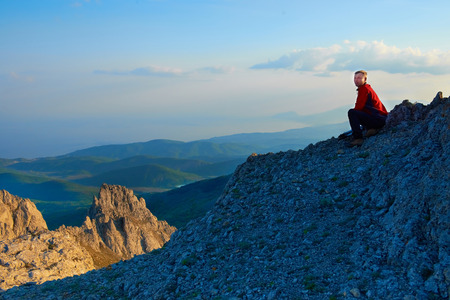 Man sitting on the rock. Sunset in the mountains, sun and blue background fog photo