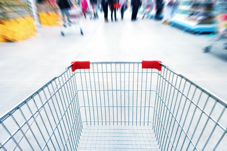 Empty trolley in supermarket or mall full of crowded people. Blur motion.