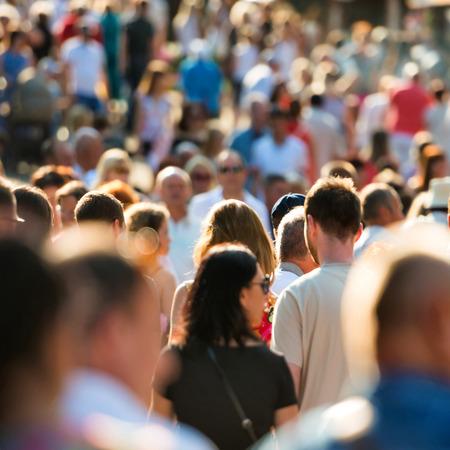 lidé: Dav lidí, kteří jdou na rušné ulici města.