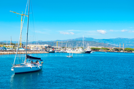 luxury travel: Recreation sail boat with people near the shore. Blue sea on the background