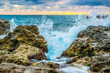 granola: Toque de la gran ola en la costa. Mar del paisaje con la puesta del sol