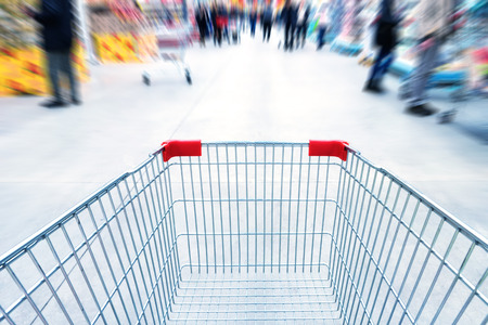 buyer: Empty trolley in supermarket or mall full of crowded people. Blur motion.