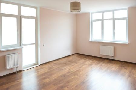 Lichte lege kamer met grote witte geïsoleerde ramen en houten vloer