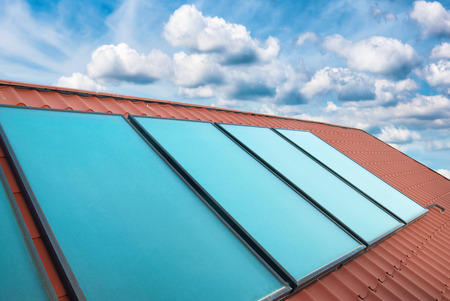 gelio: Solar cells on the red house roof over blue sky with clouds