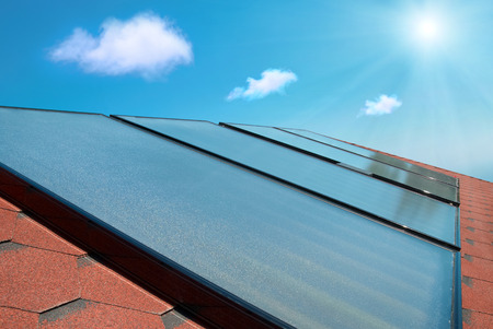 gelio: Solar water heating cells on the red house roof under shining sun and clouds. Stock Photo