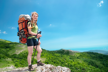 Happy young hiking woman with backpack on the mountain