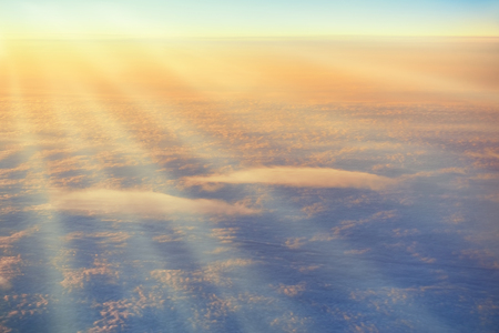 beam: Sun rays on the sky with clouds. Plane view above the earth, can be used for background
