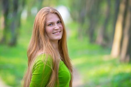 cabello rubio: Mujer bastante feliz con el pelo largo de color rojo en el parque verde de la primavera