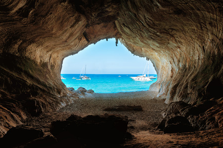 View from inside of big cave to the beach and blue sea. Mediterranean coast, Sardinia, Italy.
