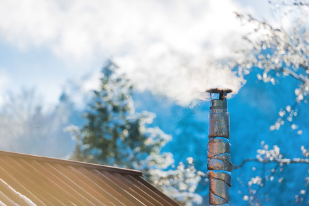 flue season: Smoke from the chimney on the roof at sunny day Stock Photo