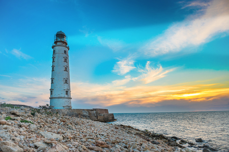 lighthouse at night: Lighthouse searchlight beam through sea air at night. Seascape at sunset