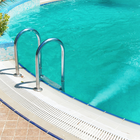 inground: Swimming pool with stair and blue relaxing water in a hotel