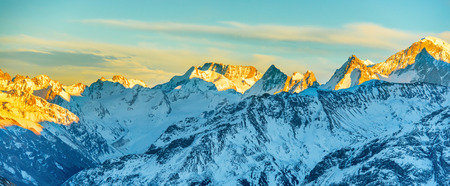 sunrise mountain: Panorama of high mountains peaks at sunset. Landscape on snow hills