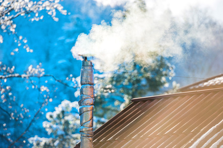 roof light: Smoke from the chimney on the roof at sunny day Stock Photo