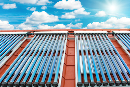 gelio: Vacuum collectors- solar water heating system on red roof of the house. Sun rays, blue sky with white clouds above
