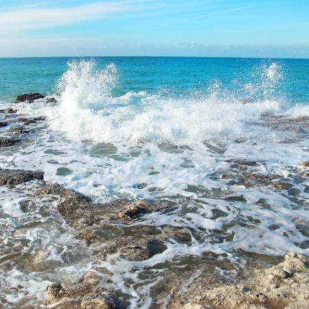 granola: Grandes olas rompiendo en las rocas. Paisaje de mar azul