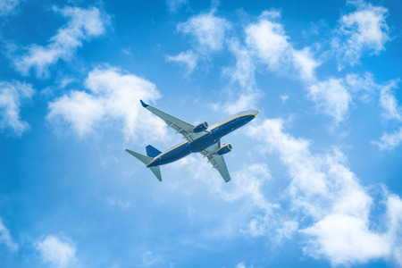 planes: A plane flying in the blue sky with white clouds Stock Photo