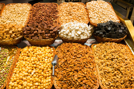 Various nuts in wooden baskets for sale at market Stock Photo