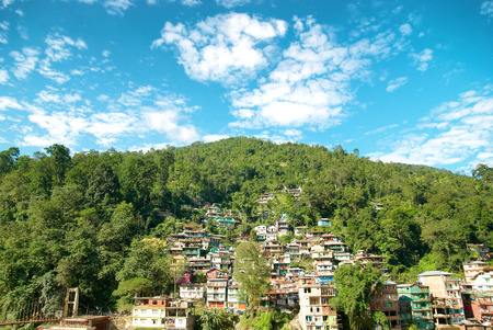 town houses: Houses in a town on green hill. India, Sikkim, Gangtok Stock Photo