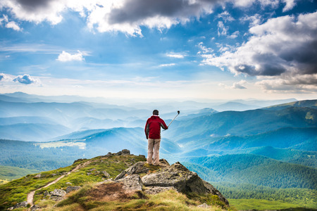 pro: Young man on the top of mountain taking picture with camera on selfie stick