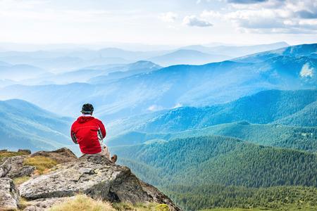 El hombre joven se sienta y medita en la parte superior de la montaña