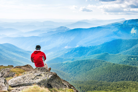 青空: Young man sits and meditates on the top of mountain