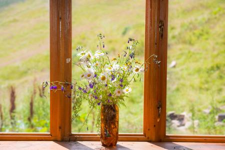 arreglo floral: Ramo de flores blancas margaritas en el alféizar de la ventana de madera en el hogar