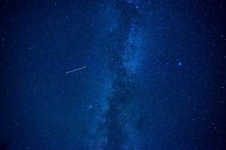 dark sky: Night dark blue sky with many stars of milky way galaxy and flying satellite Stock Photo