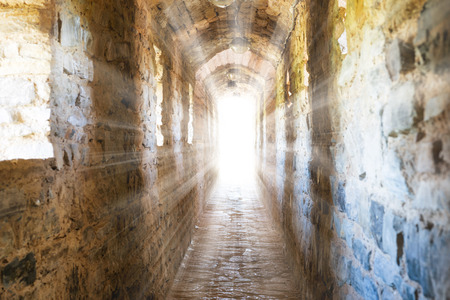 dungeon: Dark corridor in dungeon with sun rays of light in the end Stock Photo
