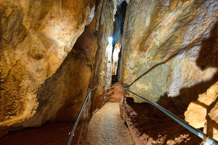 Tourist path in a beautiful old dark cave with many stalactites. Grotte di Is Zuddas, Italy, Sardinia