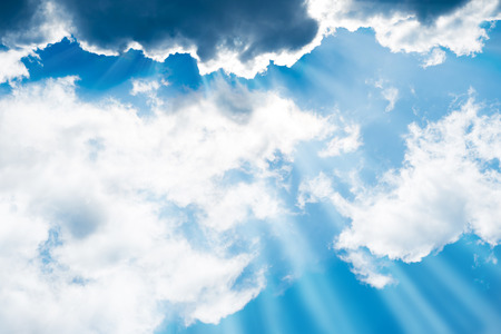 fluffy clouds: White fluffy clouds on the blue sky with sun rays. Nature background