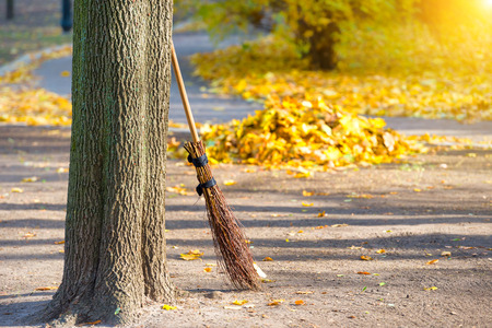 brooming: Cleaning in the autumn park - broom with pile of yellow fallen leaves