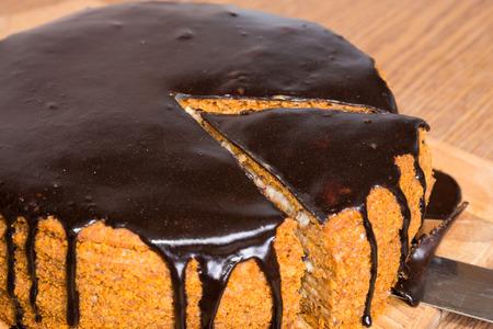 Sliced chocolate birthday cake isolated on white background