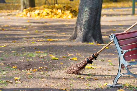 brooming: Cleaning in the autumn park - broom and bench with pile of yellow fallen leaves